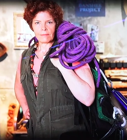 Jaclyn Ogden from the Pandora Conservation Initiative stands with a bundle of purple rope on her shoulder, wearing a green cargo vest
