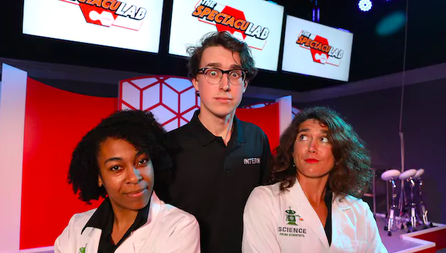 Two women wearing lab coats stand in front of a young male intern wearing a black polo shirt and glasses on stage at the Spectaculab attraction at Epcot