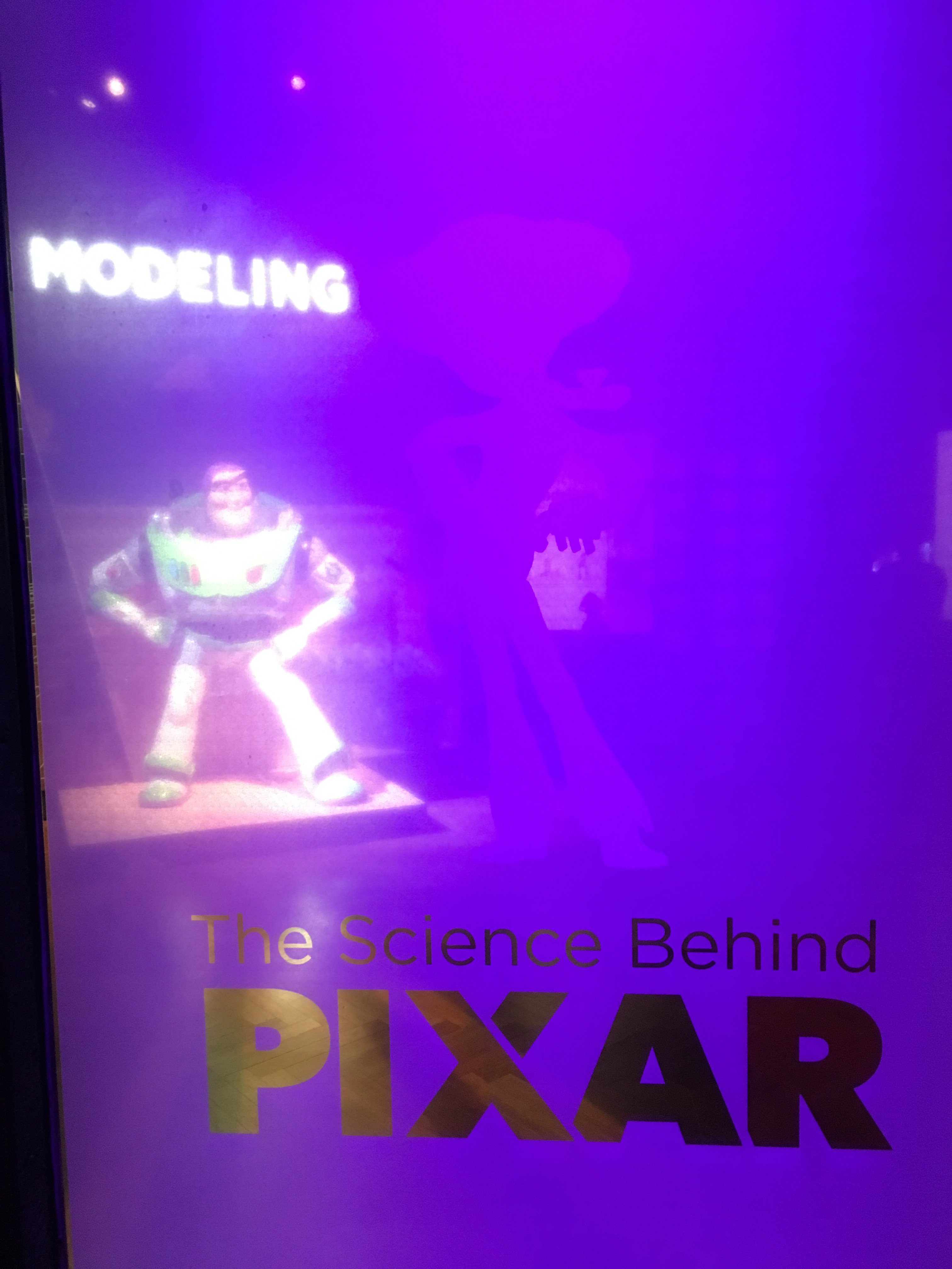 Frosted glass door that says The Science Behind Pixar with a statuette of Buzz Lightyear visible behind it