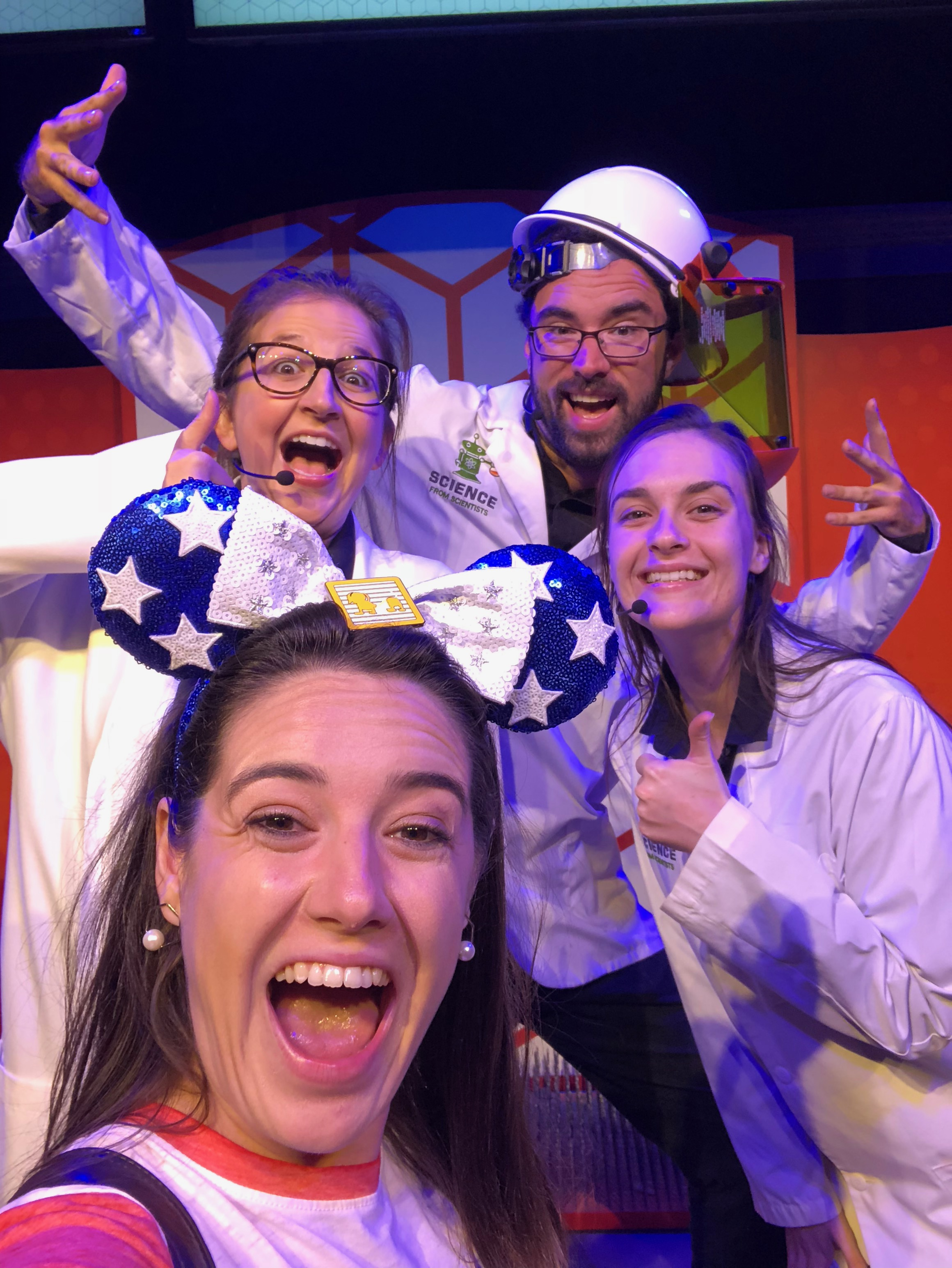 Sarah taking a selfie with the cast of SpectacuLab, who are all dressed in lab coats