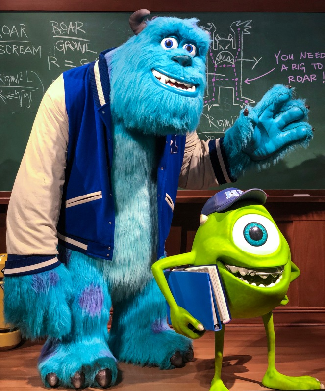 Mike and Sulley from Monster's University standing in front of a blackboard