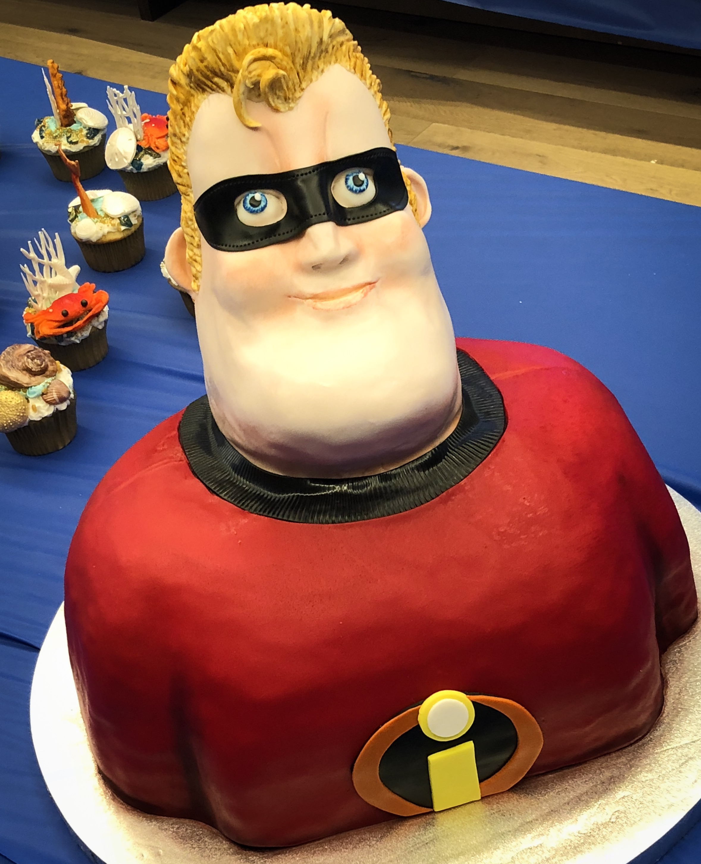 A fondant cake of Mr. Incredible's bust in his supersuit and mask