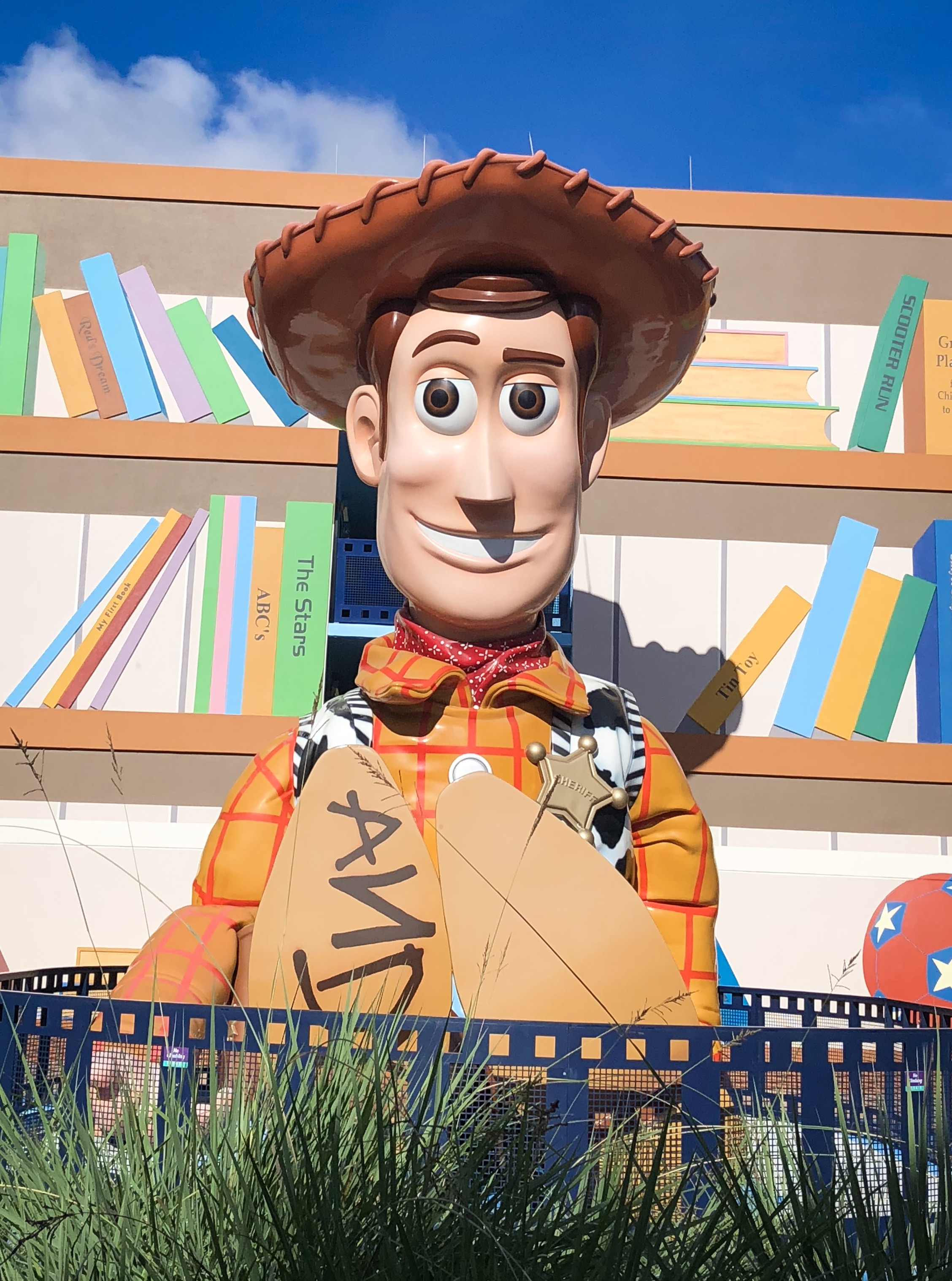 Gigantic Woody toy statue sitting in front of bookshelf
