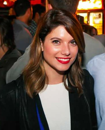 Cristina Segalin profile picture - she wears a black suit jacket with leather detail and white blouse