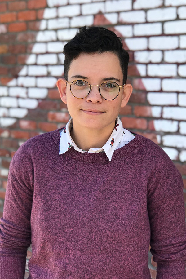 Jennifer Perez profile picture, she wears a heathered pink sweater over a white collared shirt with a fun print and is standing in front of a painted brick wall