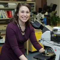 Sara Blosser stands by a microscope wearing an eggplant colored dress and smiling