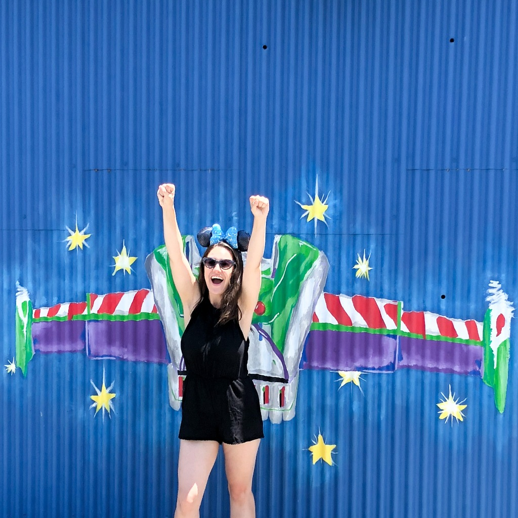 Sarah poses in front of a wall with Buzz's wings painted on it, pretending as if she's flying off to infinity and beyond.